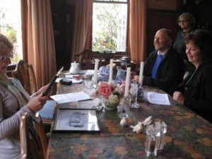 Members of Bideford congregation sitting round table, holding meeting